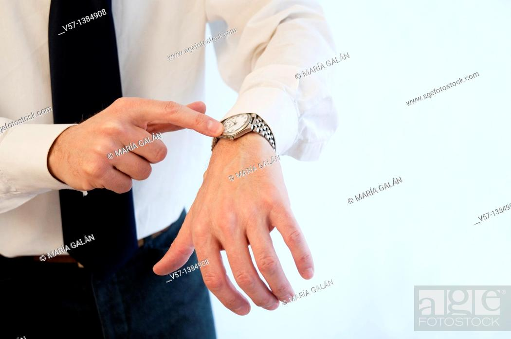Stock Photo: Man's hand pointing his watch. Close view.