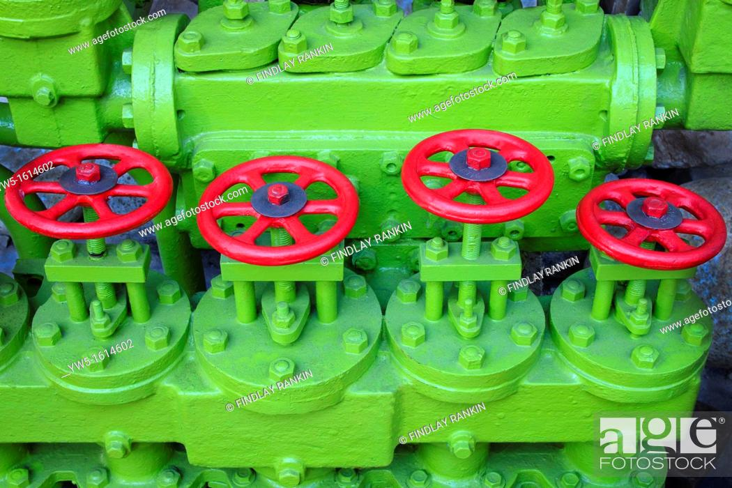 Stock Photo: Green painted engine with four red painted round handled valve controls.