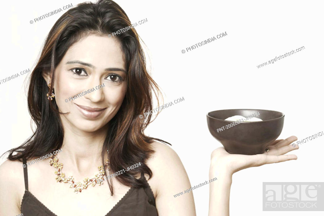 Stock Photo: Portrait of a young woman holding a bowl of food.