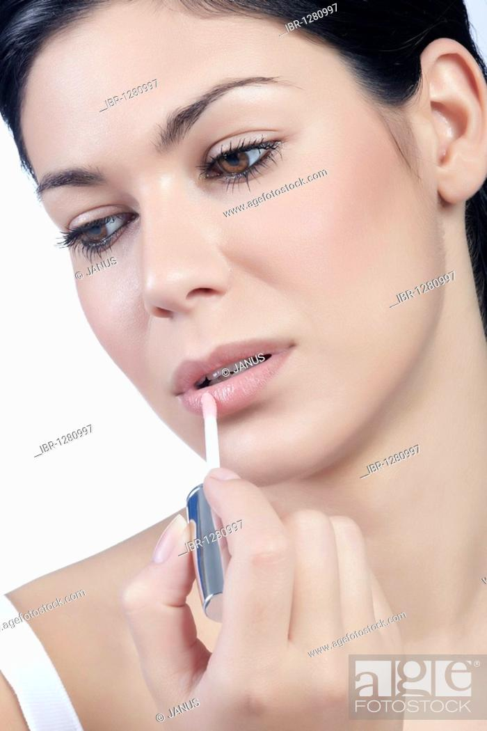 Stock Photo: Young woman applying lip gloss, beauty.