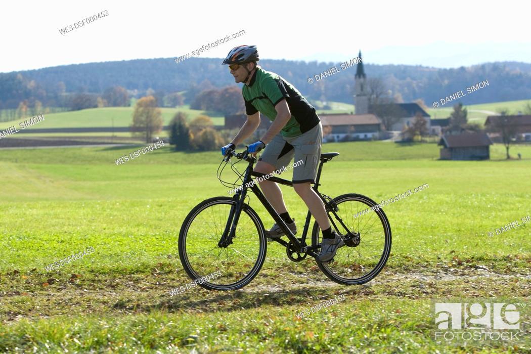 Stock Photo: Germany, Bavaria, Mature man riding bicycle.