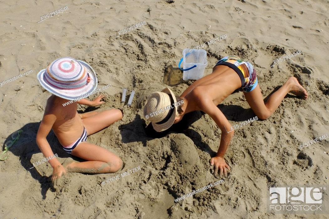 Stock Photo: A boy and girl at play on the beach of Grau d'Agde, France.