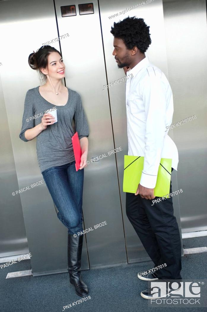 Stock Photo: Businesswoman holding a disposable cup and talking to her colleague.