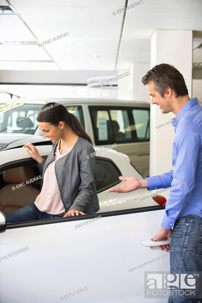 Stock Photo: Young woman checking car from inside while man holding the door.