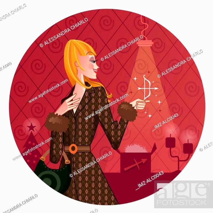 Stock Photo: A Sagittarius woman holding a small bow and arrow with a Christmas scene behind her.