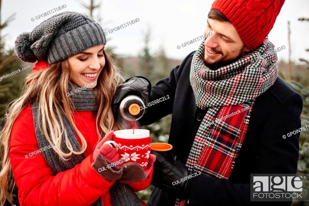 Photo de stock: Young couple pouring coffee while shopping for christmas tree from forest.