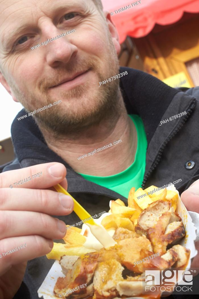 Stock Photo: Michael is eating a curry sausage with french fries at the festival of the curry sausage in Neuwied, Germany, 27 January 2017.