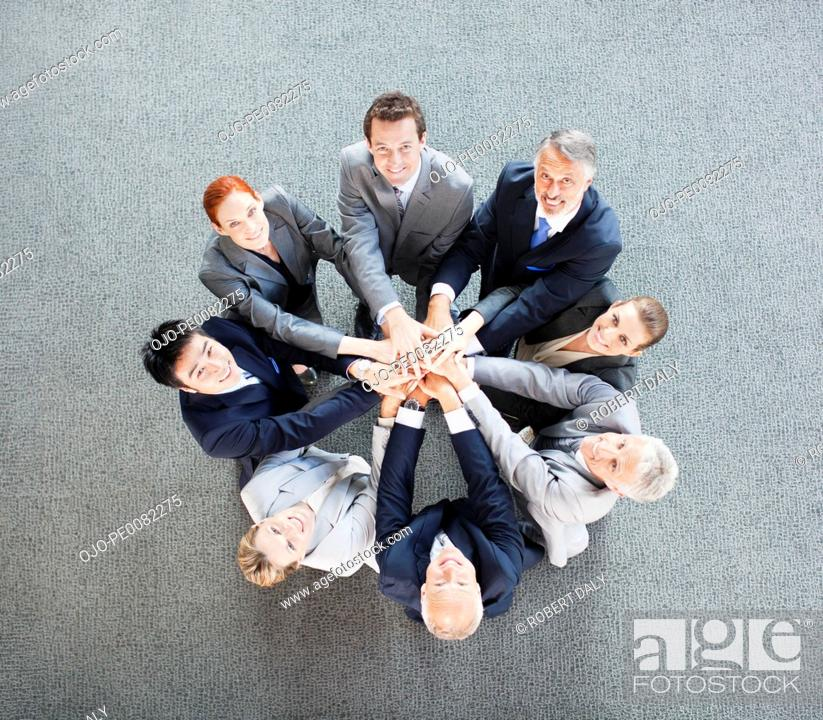 Stock Photo: High angle view portrait of business people joining hands in circle.