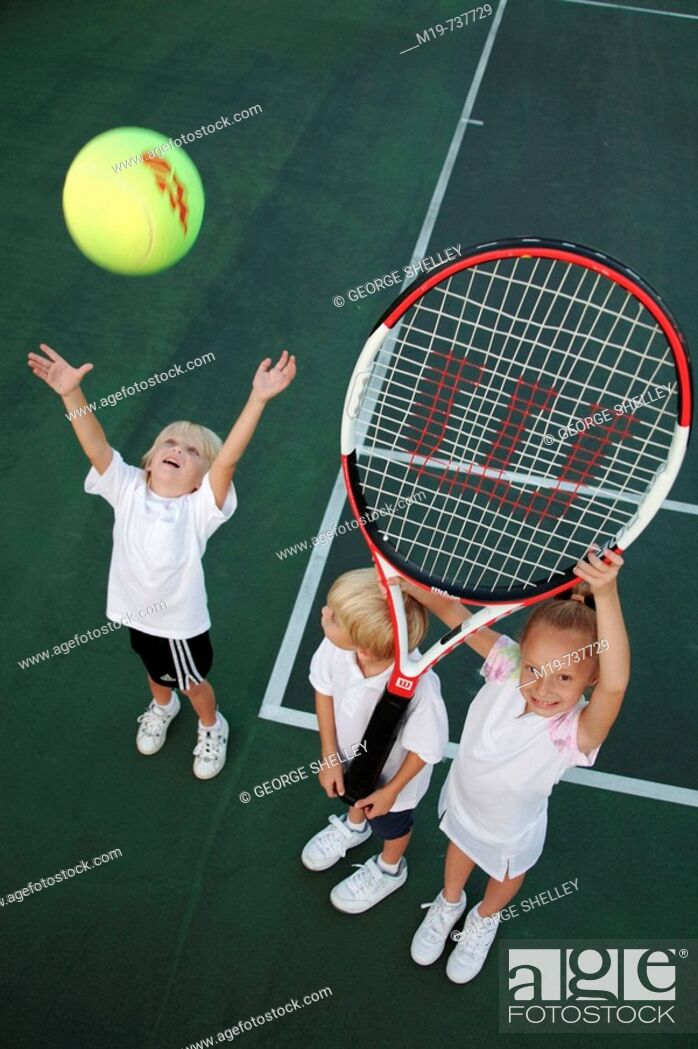Stock Photo: Kids playing with an oversized tennis racket and ball.