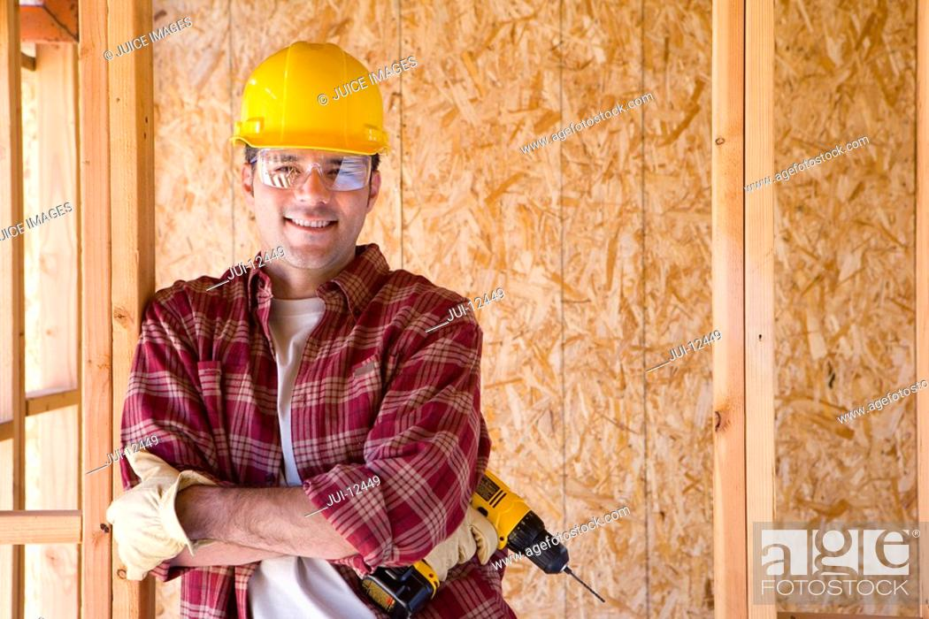 Stock Photo: Builder in hardhat with drill in partially built house, smiling, portrait.