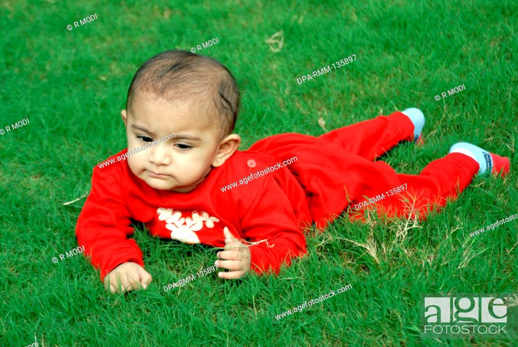ece036576815 Indian baby boy in red dress crawling playing on green grass