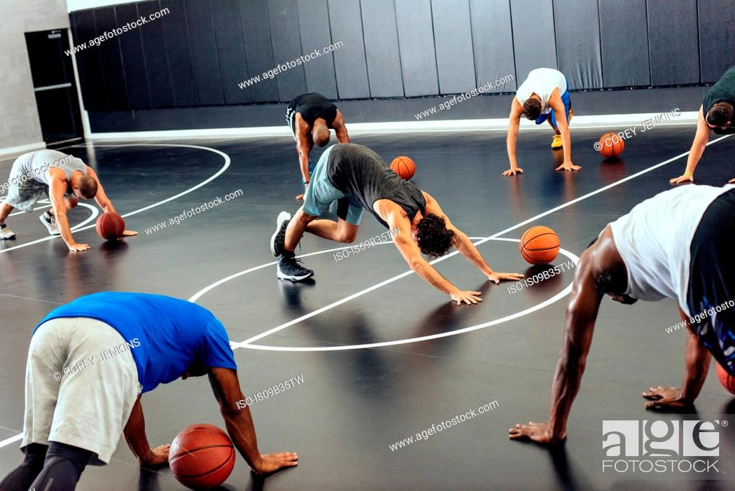 Stock Photo: Male trainer and basketball team warming up on court.