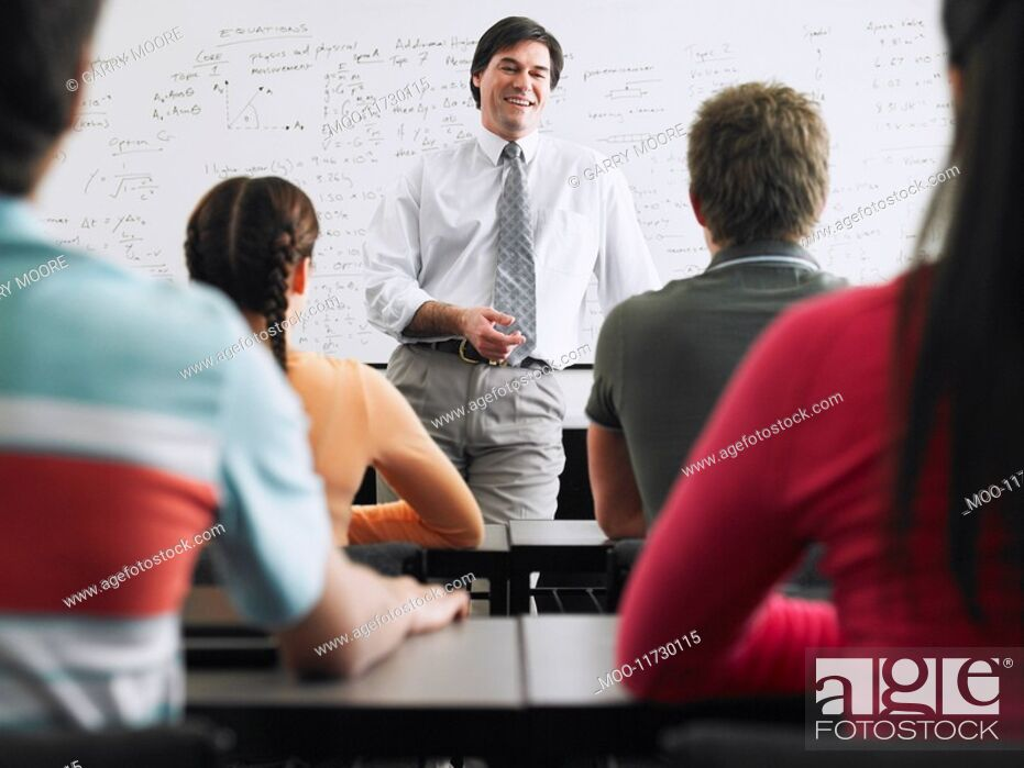 Stock Photo: Teacher talking to students in classroom.