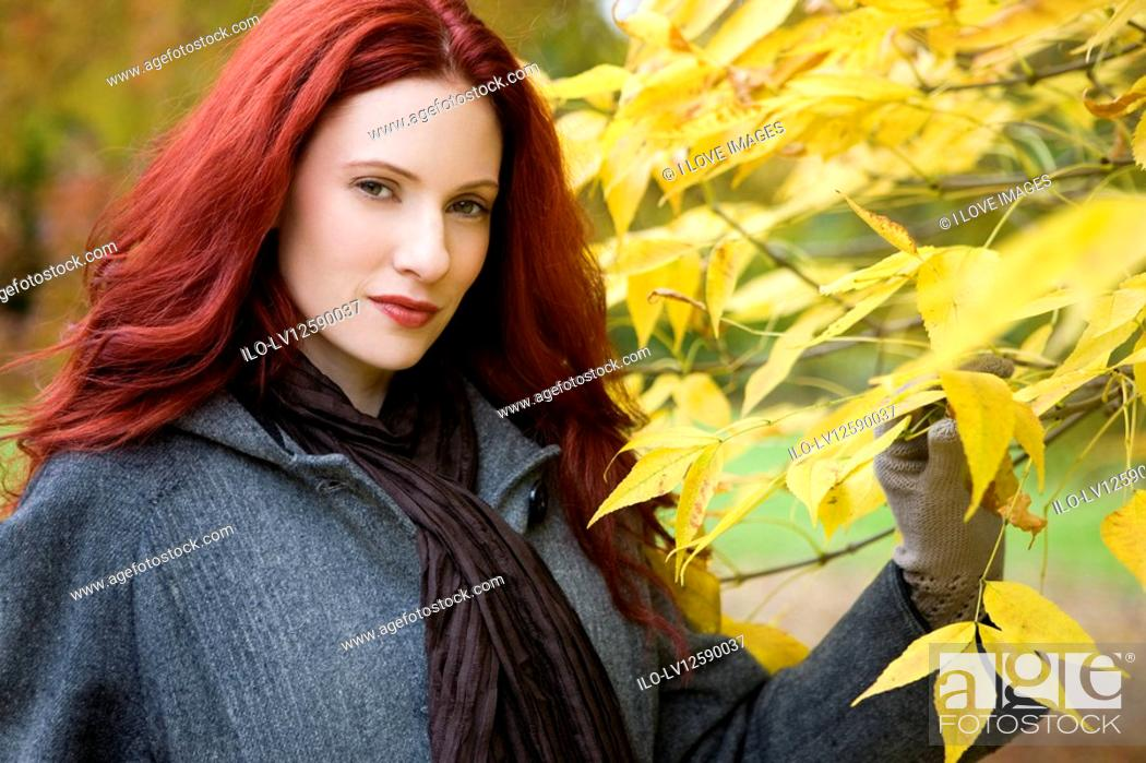 Stock Photo: A young woman standing next to a tree.