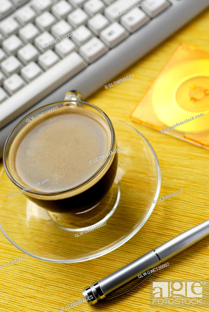 Stock Photo: Close-up of a cup of black coffee and a pen.