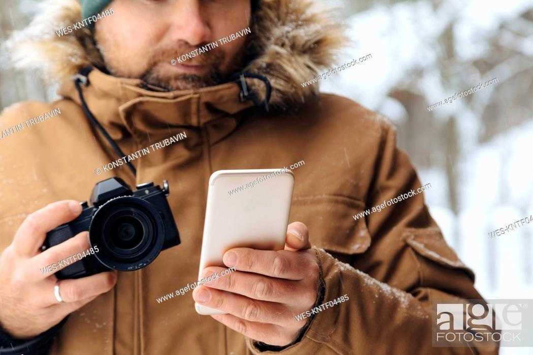 Imagen: Crop view of man with digital camera looking at cell phone in winter.