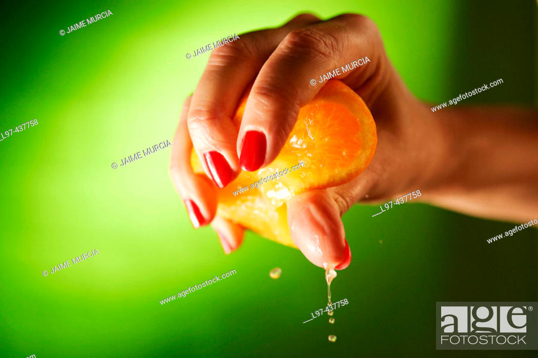 Stock Photo: Women's hand squeezing an orange.