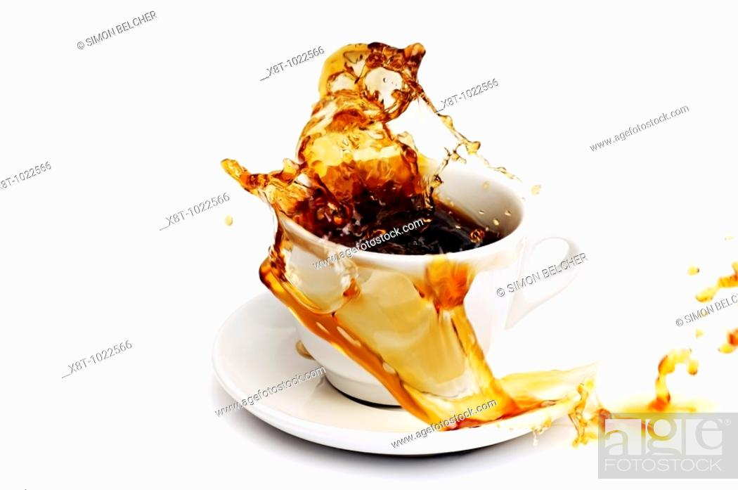 Stock Photo: Coffee Spilling from a Cup Against a White Background.