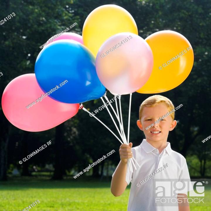 Stock Photo: Portrait of a boy holding balloons and smiling.