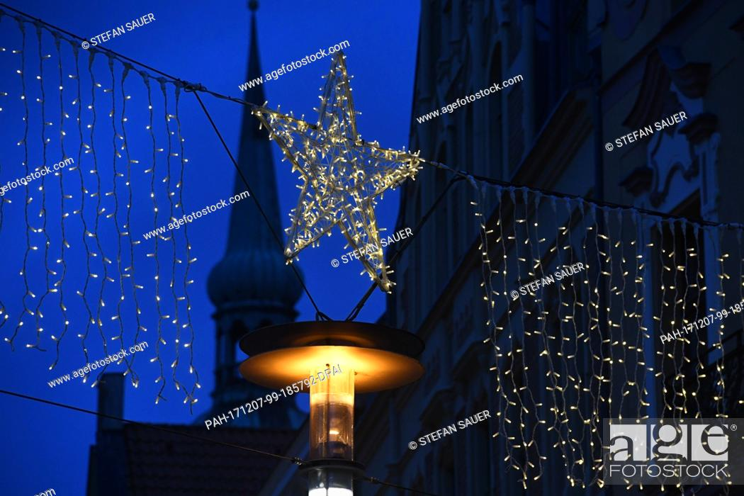 Stock Photo: View of the shopping street Ossenreyerstrasse decorated with Christmas lights during the Advent season in Stralsund, Germany, 6 December 2017.