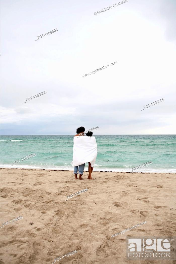 Stock Photo: A young couple wrapped in a beach towel standing on the beach.