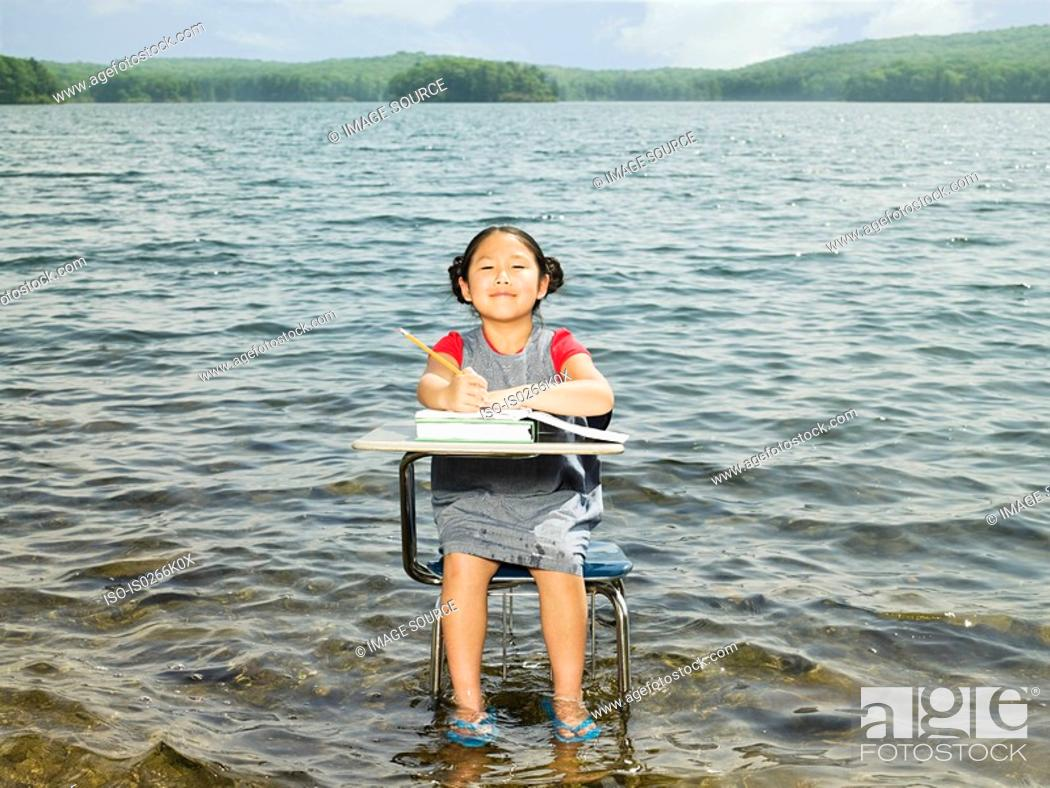Stock Photo: A girl sat at a desk in a lake.