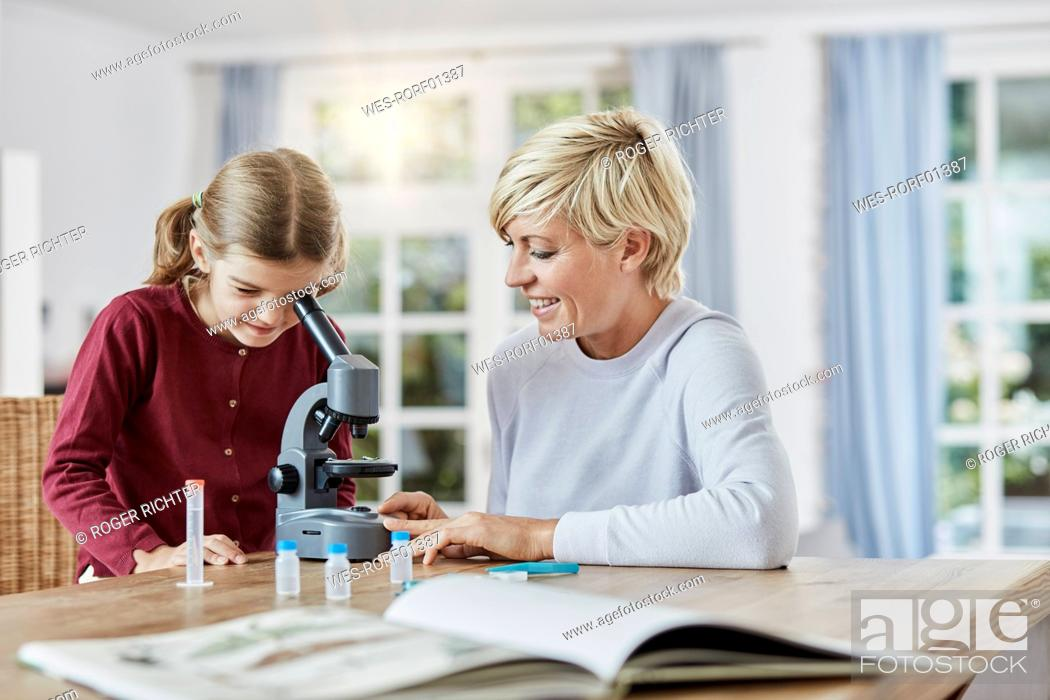 Stock Photo: Mother and daughter using microscope at home.