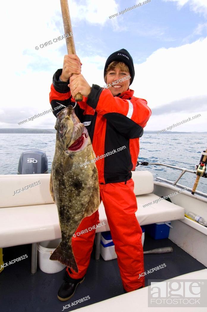 Stock Photo: Woman displays halibut while Sport fishing at Langara Island Lodge, Queen Charlotte Islands, British Columbia, Canada.