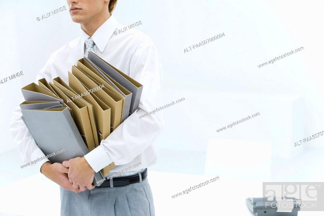 Stock Photo: Office worker carrying many binders, cropped view.