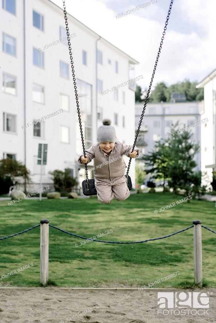 Stock Photo: Boy having fun on swing in playground.