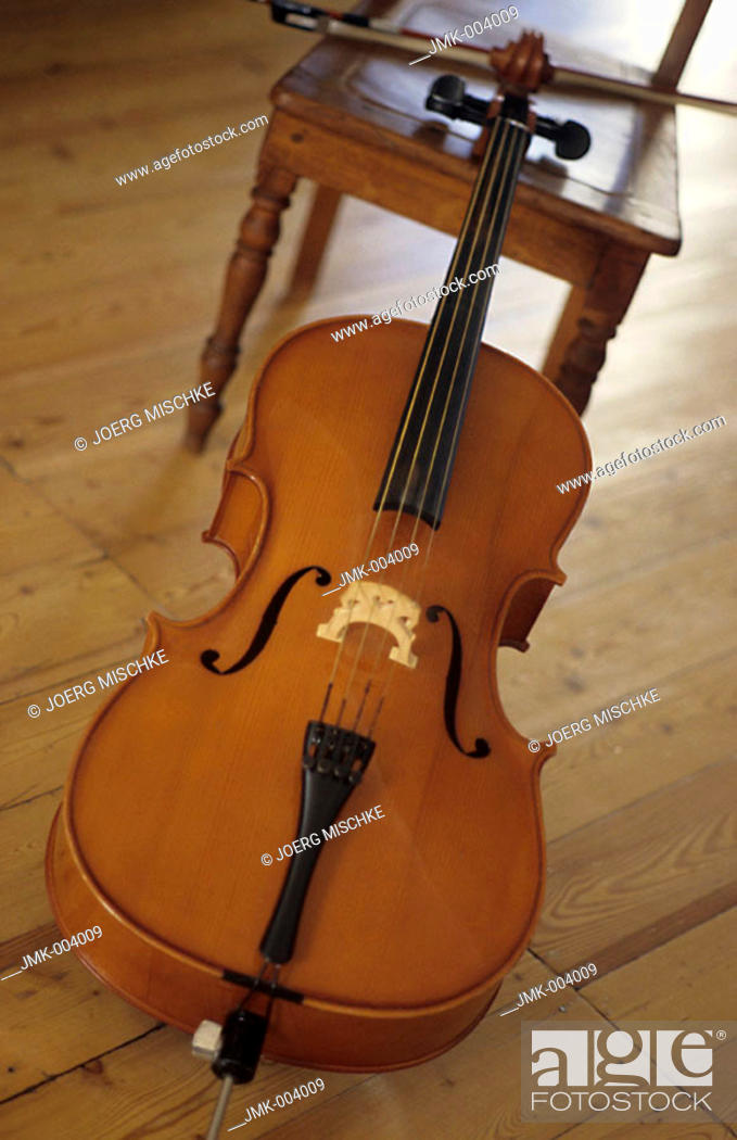 Stock Photo: A violoncello leaning against a chair in a room.