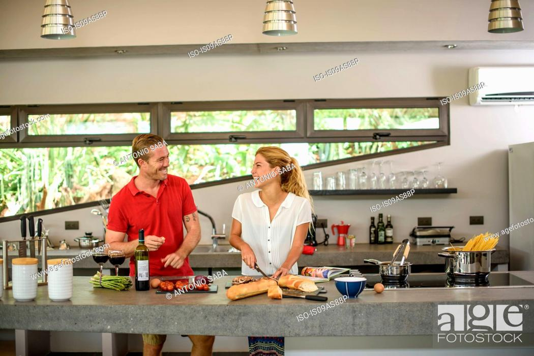 Stock Photo: Couple preparing food together in kitchen.