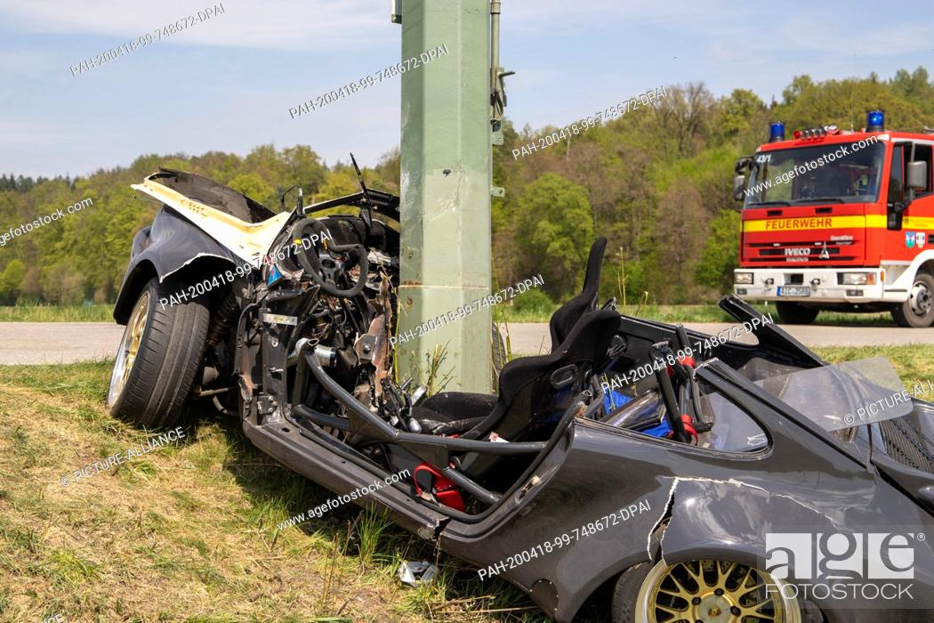 Stock Photo: 18 April 2020, Bavaria, Derching: A power pole sticks out of a Porsche after the latter has gone off the road in a slight right-hand bend and crashed into the.