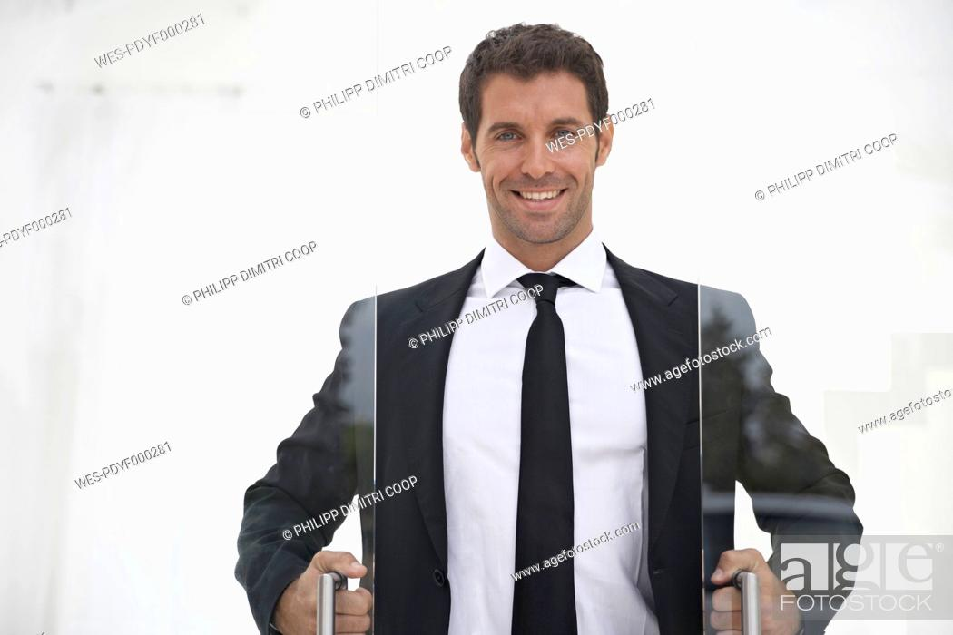 Stock Photo: Spain, Businessman opening sliding door.