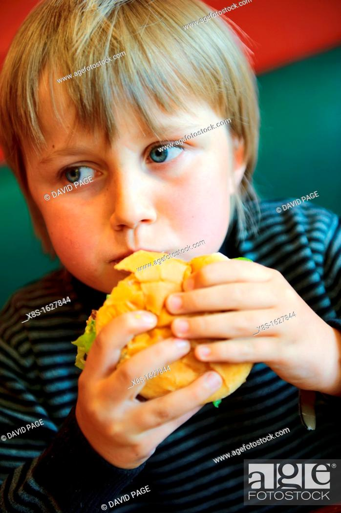 Stock Photo: Stock photo of an 11 year old boy eating a burger.