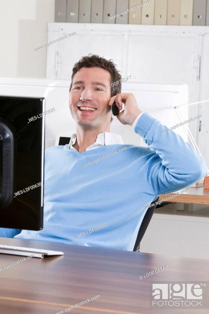 Stock Photo: Germany, Munich, business man in office using mobile phone, smiling, portrait.