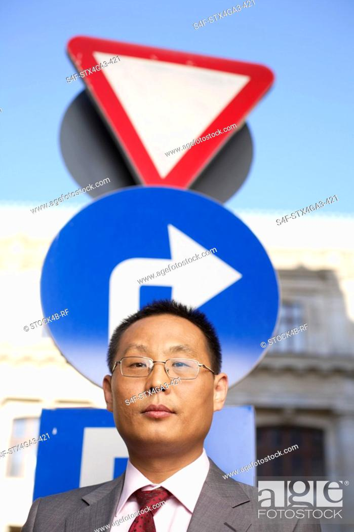 Stock Photo: Businessman in front of a traffic sign.