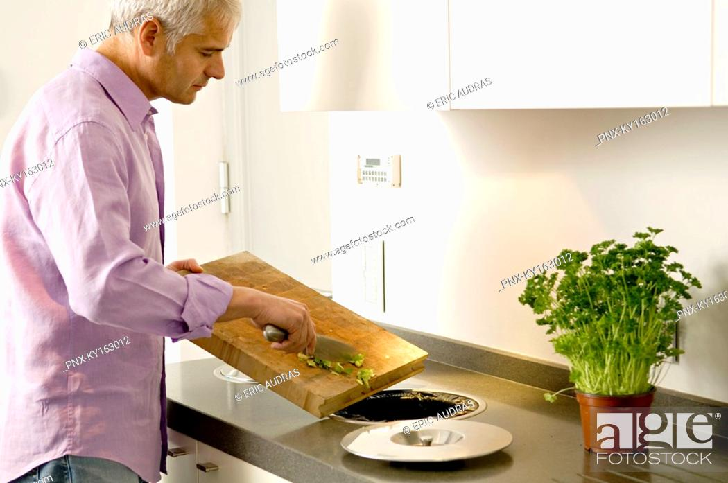 Stock Photo: Mature man scraping vegetables pieces into a garbage bin.