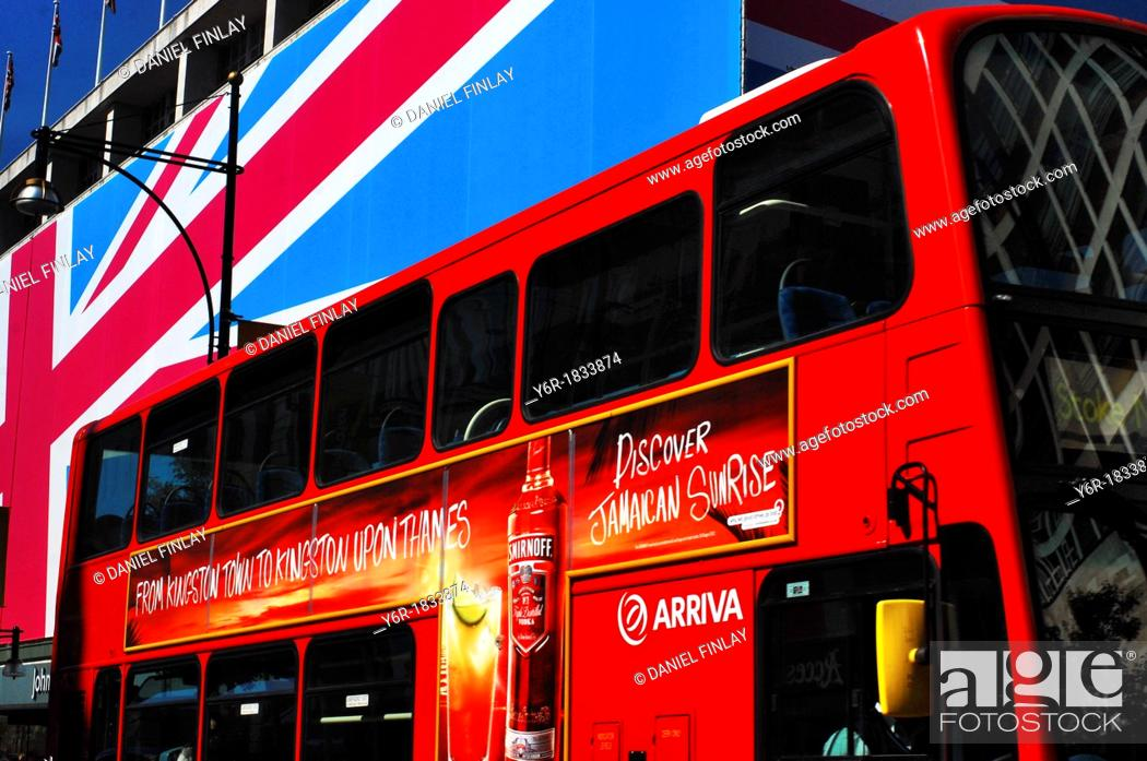 Stock Photo: Oxford Street view during the London 2012 Olympics with the Union Flag draped John Lewis department store and a red London double-decker bus.