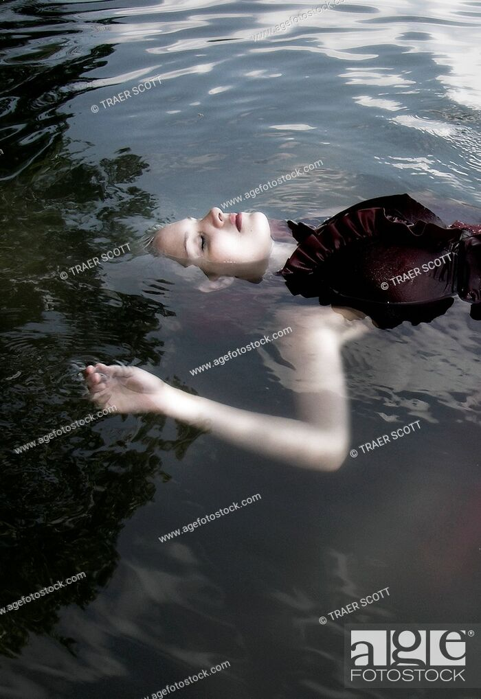 Imagen: Young woman full body floating clothed in lake.