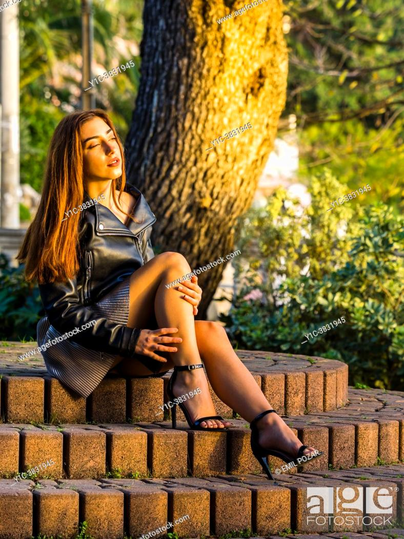 Stock Photo: Teen girl outdoors in park sitting on steps sunbathe warm light.