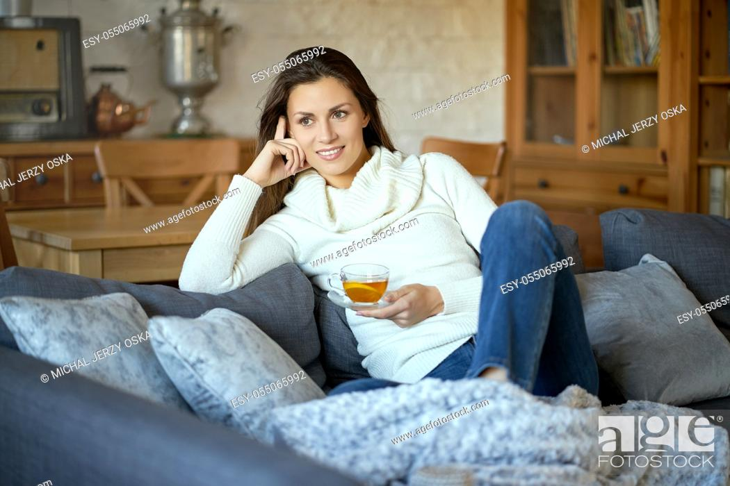 Stock Photo: attractive young woman in sweater relaxes on a gray sofa at home and drinks tea with lemon.