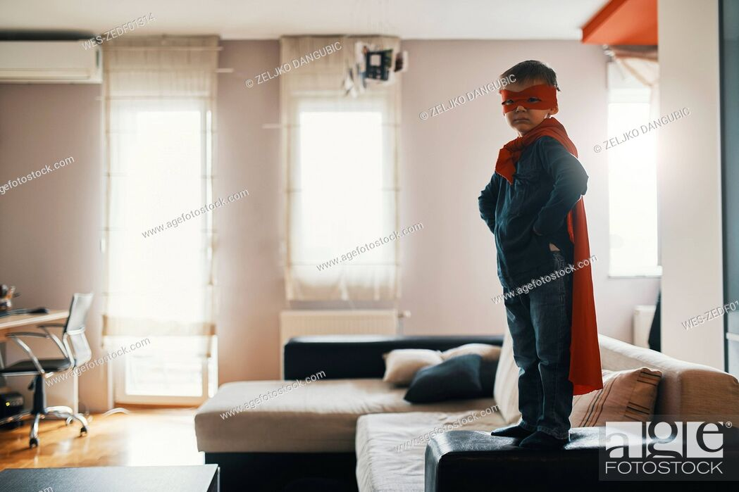 Stock Photo: Little boy dressed up as a superhero standing on coffee table at home.