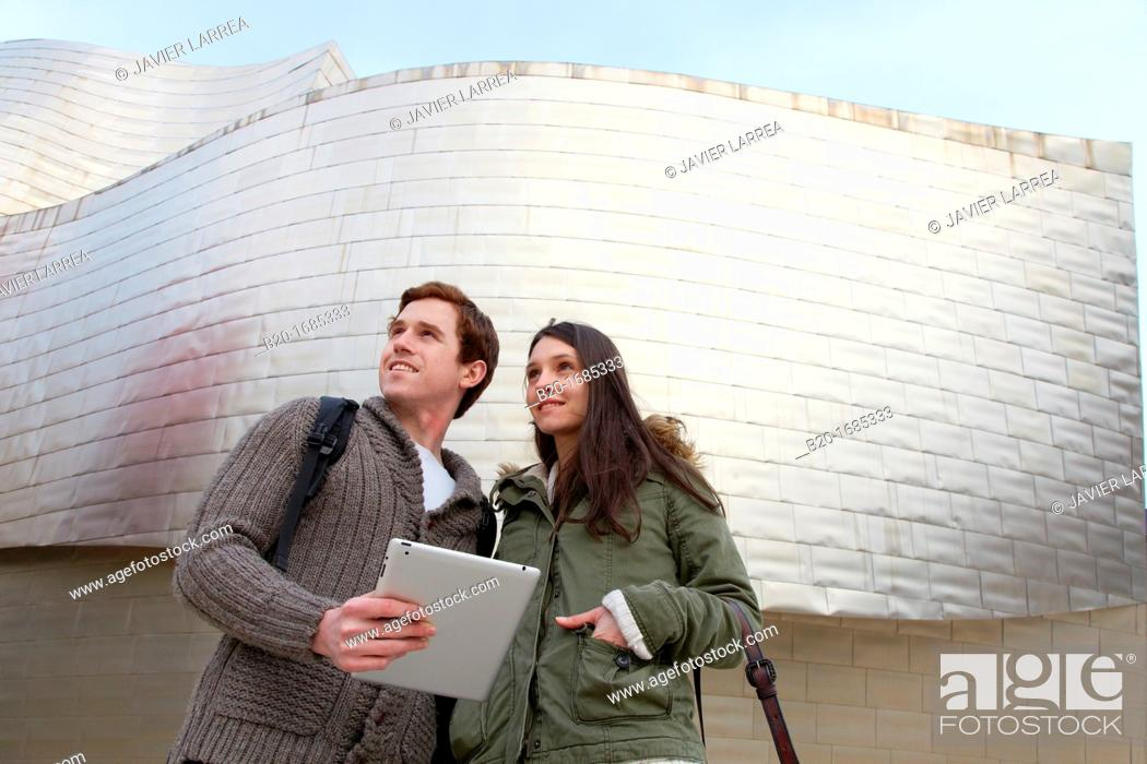 Stock Photo: Young couple looking digital tablet in the city, digital tablet, Guggenheim Museum, Abandoibarra, Bilbao, Bizkaia, Basque Country, Spain.