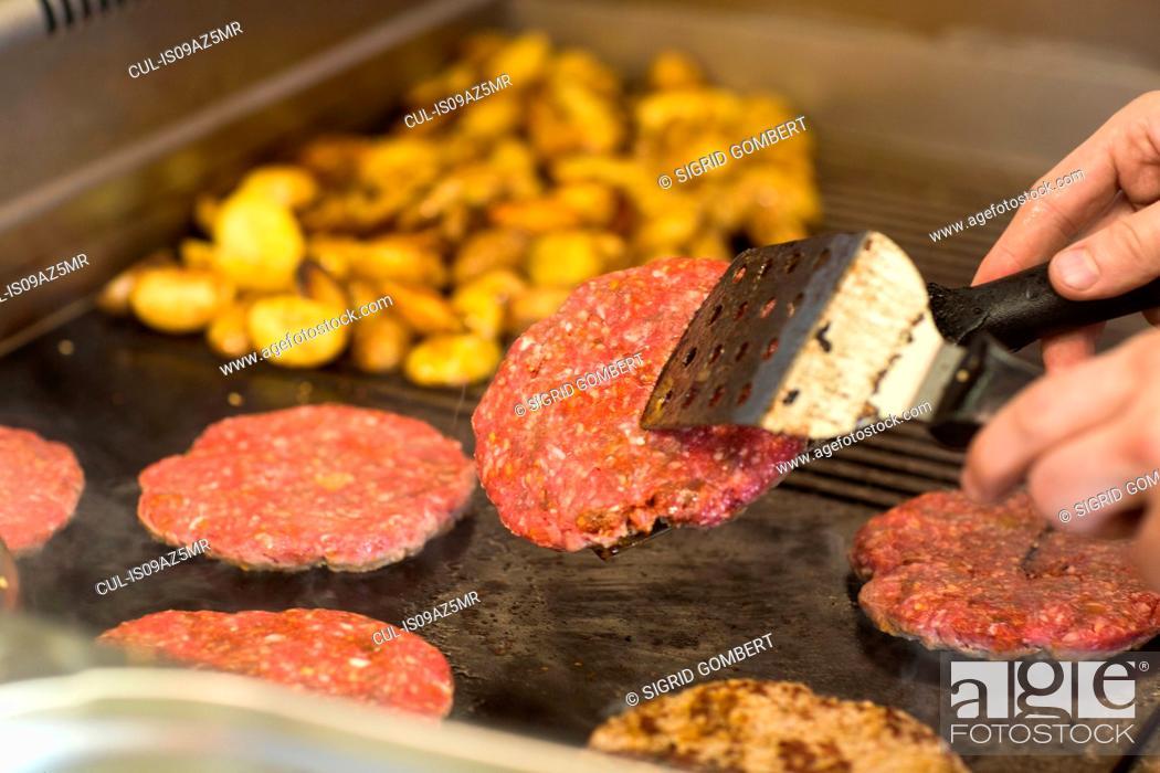 Stock Photo: Man's hand frying burger on fast food van.