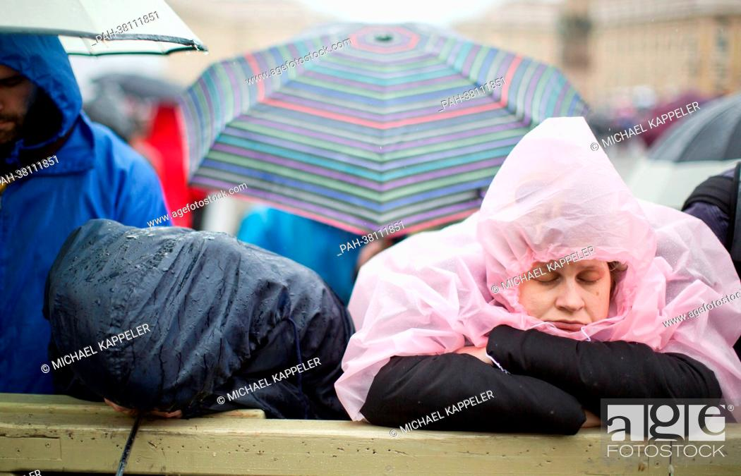 Stock Photo: Tired believers wait at St. Peter's Square for smoke to rise from the chimney of the Sistine Chapel in the Vatican, 13 March 2013.