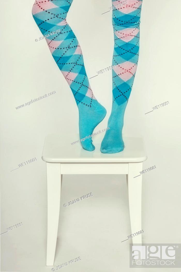 Stock Photo: legs of a woman in burlington socks on a white stool.
