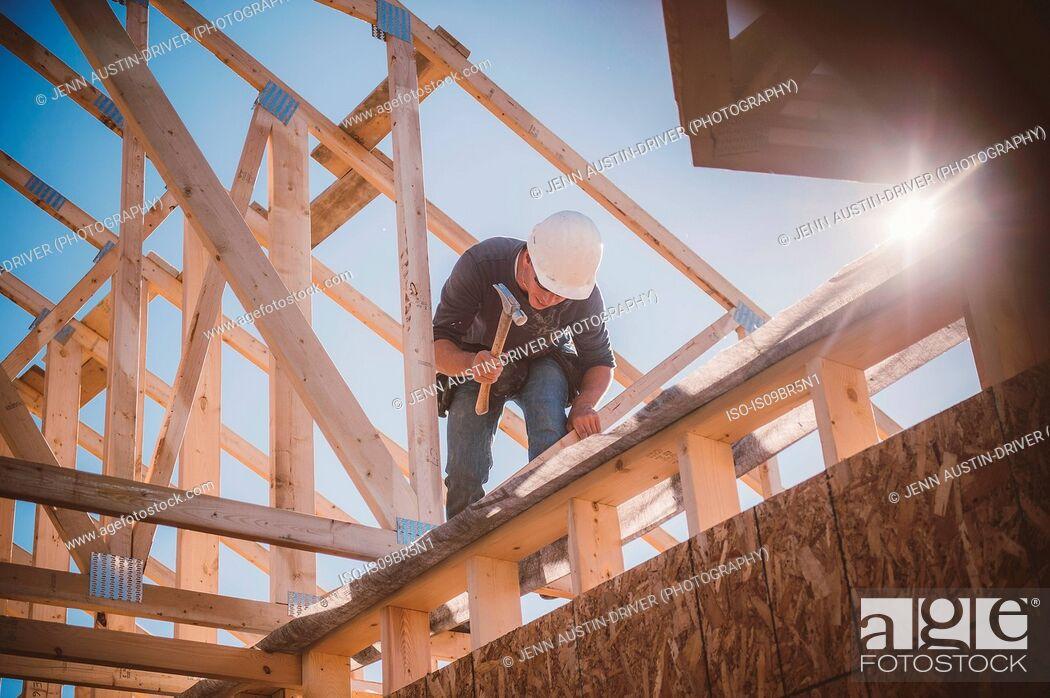 Photo de stock: Builder working on rooftop frame of building.