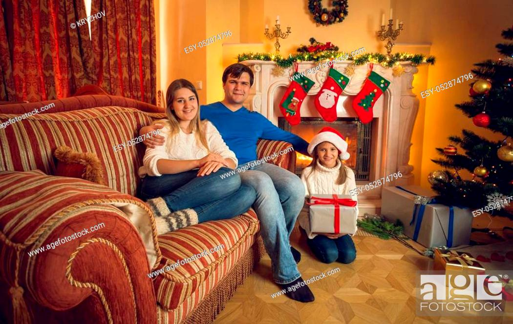 Photo de stock: Happy young family with daughter posing at living room with fireplace.