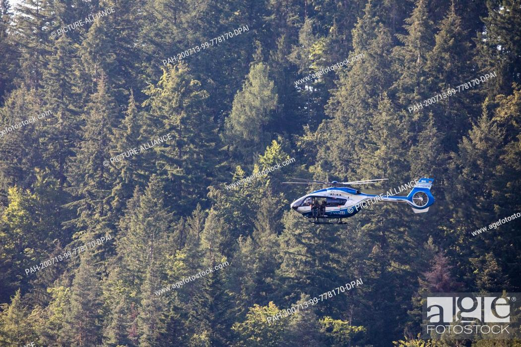 Stock Photo: 13 July 2020, Baden-Wuerttemberg, Oppenau: A police helicopter flies over the forest near Oppenau. With a large contingent.